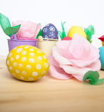 Easter colored eggs in colorful buckets and paper flowers Stock Photo