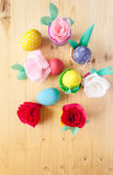 Easter colored eggs in colorful buckets and paper flowers Stock Images