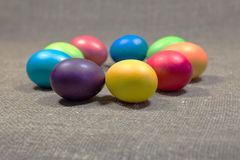 Easter colored eggs on dark green rough cotton texture art conce Stock Images