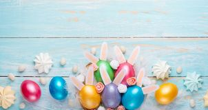 Easter colored eggs with ears of sweets and rabbit ears. Fly lay lay. Easter festive background stock photo