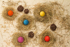 Easter colored eggs in the hay. Little newborn chick. Easter eggs in the hay. Little newborn chick on the blackboard Royalty Free Stock Photography