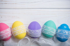Easter colored eggs with lace ribbon on white wooden background Royalty Free Stock Photos