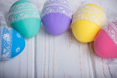 Easter colored eggs with lace ribbon on white wooden background Stock Image