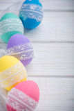 Easter colored eggs with lace ribbon on white wooden background Royalty Free Stock Photo
