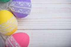 Easter colored eggs with lace ribbon on white wooden background Royalty Free Stock Image