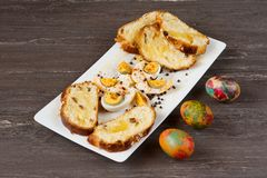 Easter colored eggs and sliced Easter bread in white plate on grey wooden board. Stock Image