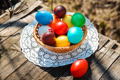 Easter colored eggs in a wicker basket on white lace napkin. On a wooden table are colored Easter eggs in a wicker basket on white lace napkin. One red egg is Stock Image