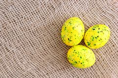 Easter colored eggs yellow with green splashes. On linen brown fabric royalty free stock images