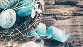 Easter. Colorful blue eggs and spring snowdrop flowers over wooden background. Easter holiday greeting card stock photos