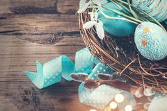 Easter. Colorful blue eggs and spring snowdrop flowers over wooden background. Easter holiday greeting card. With decorated handmade eggs and spring flowers stock photos
