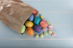 Easter colorful dyed chicken eggs in a paper bag. And sweets on a blue wooden table stock photography