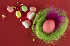 Easter colorful egg with a beautiful pink feather in a nest. stock photo