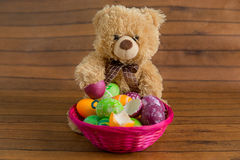 Easter colorful eggs in basket and fluffy toy bear Royalty Free Stock Photos