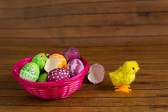 Easter colorful eggs in basket and toy chicken Royalty Free Stock Images