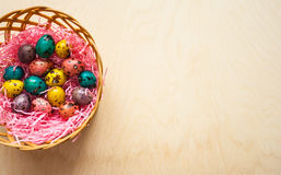 Easter. Colorful eggs in a basket  on wooden background. Happy Easter. Colorful eggs in a basket  on wooden background Stock Photo