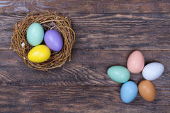 Easter colorful eggs in bird nest on wooden background Royalty Free Stock Images