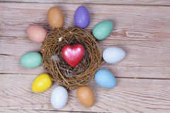 Easter colorful eggs in bird nest on wooden background Stock Photos