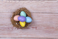 Easter colorful eggs in bird nest on wooden background Royalty Free Stock Photos