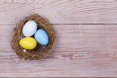 Easter colorful eggs in bird nest on wooden background Royalty Free Stock Image