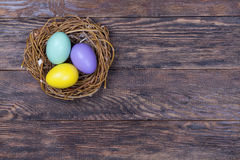 Easter colorful eggs in bird nest on wooden background Stock Photography