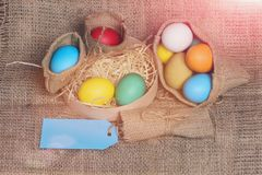 Easter colorful eggs in burlap sack and box with tag Stock Image