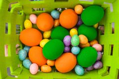 Easter colorful eggs of different sizes in a basket stock photo