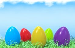 Easter colorful eggs in green grass and blue sky. Background with empty space for text. 3D illustration and renderingn Royalty Free Stock Image