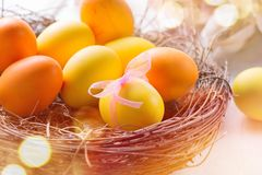 Easter colorful eggs in the nest. Beautiful painted, colorful yellow and orange color eggs with decorations on white wooden table Royalty Free Stock Photos