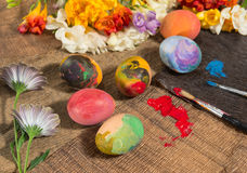 Easter colorful eggs with spring flowers and two painter's brushes. Stock Photo
