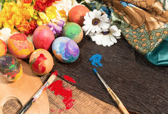 Easter colorful eggs with spring flowers and two painter's brushes. Stock Images