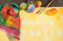 Easter colorful eggs with two painter  brushes and a hand painted cloth,arranged on watercolor paper with yellow painted text. Royalty Free Stock Photography