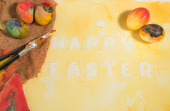 Easter colorful eggs with two painter  brushes and a hand painted cloth,arranged on watercolor paper with yellow painted text. Stock Photography