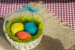 Easter colorful eggs in a white basket royalty free stock photo