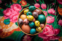 Easter. Colorful eggs in a wooden bowl  on a background of patte. Happy Easter. Colorful eggs in a wooden bowl  on a background of patterned black headscarf Royalty Free Stock Image
