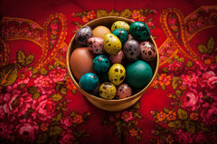 Easter. Colorful eggs in a wooden bowl  on a background of patte. Happy Easter. Colorful eggs in a wooden bowl  on a background of patterned red headscarf Stock Photo