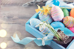 Easter colorful painted eggs with spring flowers and blue satin ribbon on wood. En table top background Stock Photo