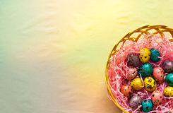 Easter colorful quail eggs in  a basket. Happi Easter. Painted eggs in a basket on the craft background Stock Photography