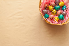 Easter colorful quail eggs in  a basket. Happi Easter. Painted eggs in a basket on the craft background Royalty Free Stock Photos