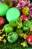 Easter coloured eggs. Surrounded by flowers on grass royalty free stock image