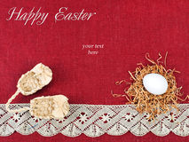 Easter composition. Nest with one white egg and small wicker shoes on wine red flax background decorated with lace Stock Photography