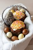 Easter concept composition with beautifully decorated Easter cake, dyed eggs, chocolate egg in a basket on linen fabric stock photo