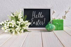 Easter composition with blackboard decorated with ceramic hen, e. Ggs and and lily of the valley flowers, caption `Happy Easter Stock Photos