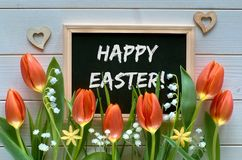 Easter composition with blackboard framed with spring flowers, t. Ulips and lily of the valley. Text `Happy Easter` on the blackboard Royalty Free Stock Image