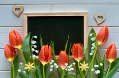 Easter composition with blackboard framed with spring flowers, t. Ulips and lily of the valley. Text `Happy Easter` on the blackboard Royalty Free Stock Photo