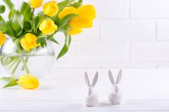 Easter composition with bouquet of yellow tulip flowers in glass vase and two white ceramic rabbits on white stock photo