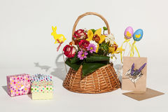 Easter composition. Bright Easter composition of bouquet in basket, colored boxes, cards and eggs Stock Image