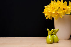Easter composition with bunnies and narcissus. Easter still life composition with bunnies figurines and yellow flowers of narcissus in vase, copyspace on black Stock Images