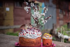 Easter composition. Easter cake decorated white icing and colorful sugar sprinkles on a concrete background. Easter sweet bread Orthodox kulich, paska, willow Stock Photo