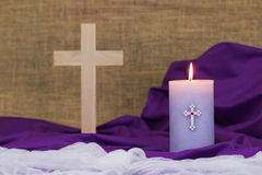 Easter composition; candle, wood cross, white and purple linen Stock Images