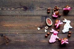 Easter composition. Easter sweet gift. Chocolate eggs near cookies in shape of Easter bunny on dark wooden background. Top view Royalty Free Stock Photos